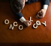 Word Oncology and devastated man composition stock photo