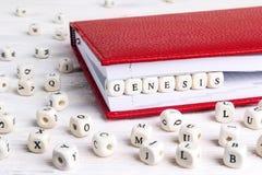 Word Ontstaan in houten blokken in rood notitieboekje op wit w wordt geschreven dat stock afbeelding