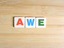 Word Ontzag op houten achtergrond stock foto's