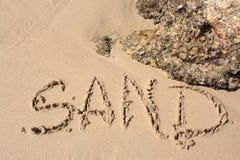 Word op het zandige strand Stock Foto