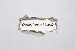 The word open your mind appearing behind torn paper Stock Photography