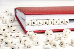 Word Oplossing in houten blokken in rood notitieboekje op wit wordt geschreven dat Stock Foto
