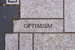 Motivational Typography Brick Sidewalk. The word optimism on a motivational brick sidewalk made of concrete and mortar Royalty Free Stock Images