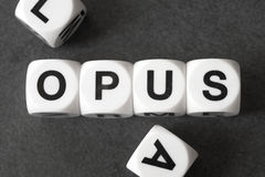 Word opus on toy cubes. Word opus on white toy cubes royalty free stock image