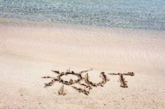 Word OUT written on sand on a beautiful beach, blue waves in background Stock Photo