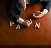 Word Pain and devastated man composition. Word Pain made of wooden block letters and devastated middle aged caucasian man in a black suit sitting at the table royalty free stock image