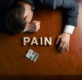 Word Pain and devastated man composition Royalty Free Stock Images