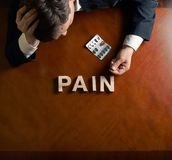 Word Pain and devastated man composition Stock Photography