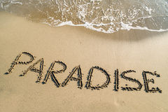 Word paradise on beach. Word Paradise on sandy beach - concept travel background Royalty Free Stock Image