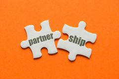 The word Partnership on two matching puzzle on orange background.  Royalty Free Stock Image
