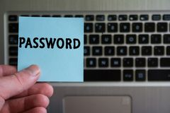 Word PASSWORD on sticky note. Hold in hand on laptop keyboard background stock image