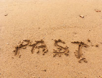 Word Past on sand. Word Past in handwriting on sandy beach Stock Image