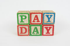 The Word Pay Day in Wooden Childrens Blocks. Pay Day - Isolated Text Word In Wooden Childrens Building Blocks with a White Background. The blocks are Stock Photos