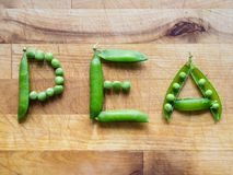 Word PEA written with peas. Word PEA created with peas on a wooden board Royalty Free Stock Images