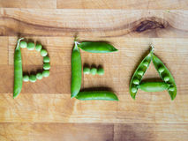 Word PEA written with peas. Word PEA created with peas on a wooden board Stock Images