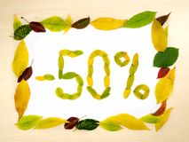 Word 50 percent made of autumn leaves inside of frame of autumn leaves on wood background. Fifty percent sale. Sale template. Word 50 percent made of autumn royalty free stock photography