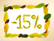 Word 15 percent made of autumn leaves inside of frame of autumn leaves on wood background. Fifteen percent sale. Sale template. Word 15 percent made of autumn stock images