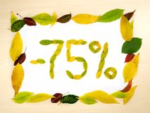 Word 75 percent made of autumn leaves inside of frame of autumn leaves on wood background. Seventy five percent. Sale template. Word 75 percent made of autumn stock image