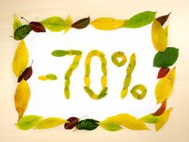 Word 70 percent made of autumn leaves inside of frame of autumn leaves on wood background. Seventy percent sale. Sale template. Word 70 percent made of autumn stock photo