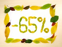 Word 65 percent made of autumn leaves inside of frame of autumn leaves on wood background. Sixty five percent sale.Sale template. Word 65 percent made of autumn stock images