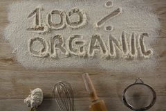 The word 100 percent organic written on sprinkled flour. Over head view of the word 100 percent organic written on sprinkled flour Royalty Free Stock Photography