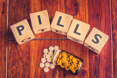 The word pills on a table. The word pills on a dark wooden table Royalty Free Stock Images