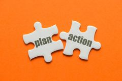 The word Plan Action on two matching puzzle on orange background.  stock photo