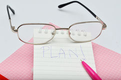 Word Plan messege on pink pen notebook with glasses Stock Photos