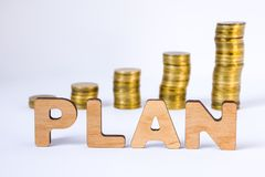 Word plan of three-dimensional letters is in foreground with growth columns of coins on blurred background. Monetary plan concept. For starting or development Stock Photo
