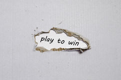 The word play to win appearing behind torn paper royalty free stock photos