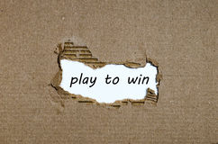 The word play to win appearing behind torn paper royalty free stock images