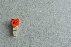 The word plus on a peg. On a white background Royalty Free Stock Photography
