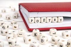 Word Poëzie in houten blokken in rood notitieboekje op witte wo wordt geschreven die Stock Fotografie