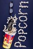 Word popcorn die op een blauwe achtergrond wordt verspreid Het concept is bioskoop Stock Afbeelding