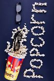 Word popcorn scattered on a blue background. The concept is cinema. Stock Image