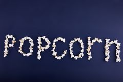 Word popcorn scattered on a blue background. Empty space for text Royalty Free Stock Images