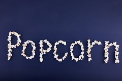 Word popcorn scattered on a blue background. Empty space for text Royalty Free Stock Photography