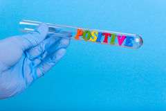 Word positive in test-tube holding a gloved hand Royalty Free Stock Photos