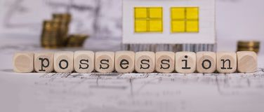 Word POSSESSION composed of wooden letter. Small paper house in the background. Closeup stock image