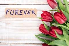 Word POUR TOUJOURS et bouquet des tulipes Photographie stock
