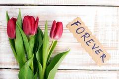 Word POUR TOUJOURS et bouquet des tulipes Photos stock