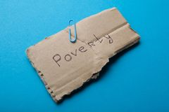 The word `poverty` on a piece of cardboard on a blue background. stock photo
