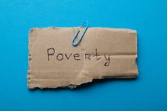 The word `poverty` written on cardboard, isolated on a blue background, concept. royalty free stock photo