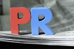 Word PR on newspaper. Wooden letters royalty free stock photos