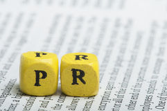 Word PR.Wooden cubes on magazine Royalty Free Stock Photos