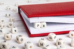 Word PR written in wooden blocks in red notebook on white wooden. Table. Wooden abc royalty free stock photography