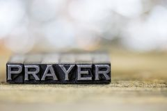 Prayer Concept Vintage Metal Letterpress Word. The word PRAYER concept written in vintage retro metal letterpress type on a wooden background Stock Photo
