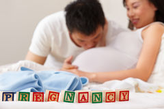 Word pregnancy in front of happy couple Stock Photo