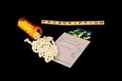 Prescription spelled out with tiles above spilled white pills over a prescription pad and colored pills on a black background. The word prescription is spelled Stock Photos