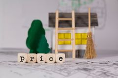 Word PRICE composed of wooden letter. Small paper house, wooden trees in the background. Closeup stock photos